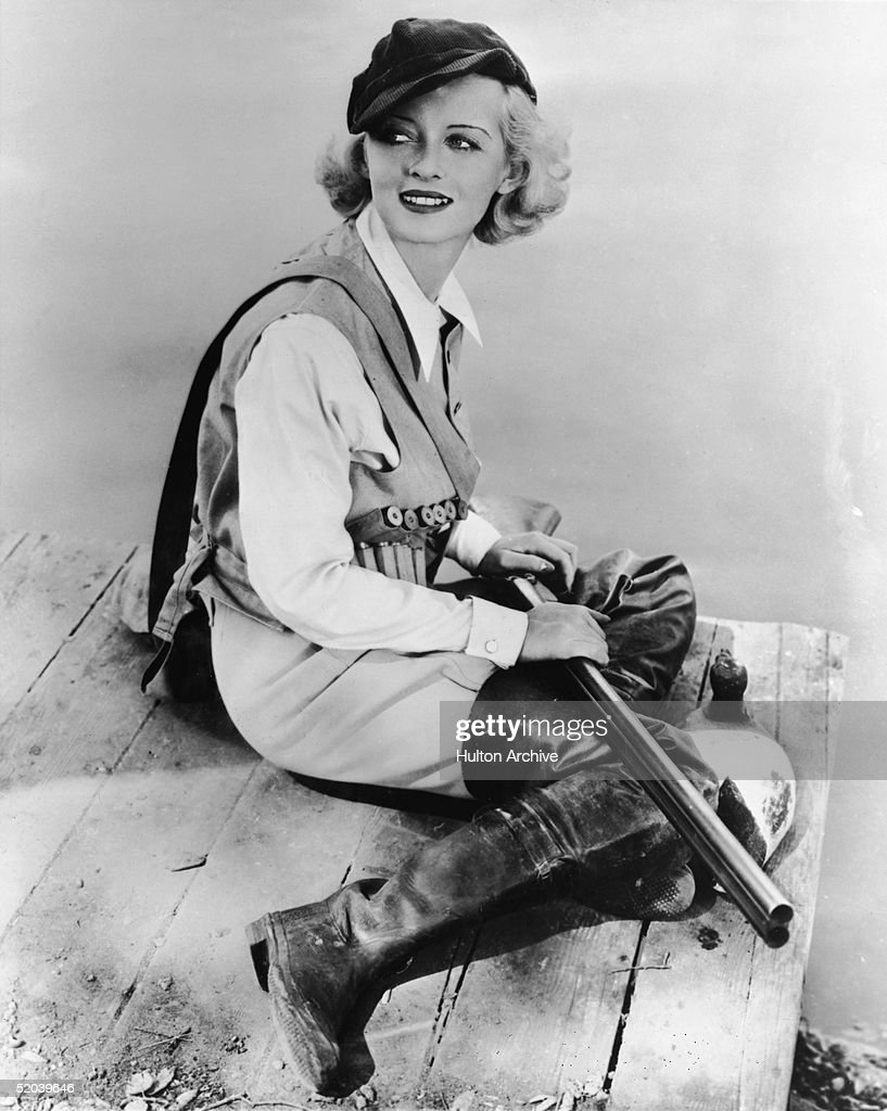 Dressed in a hunting outfit, complete with ammunition belt, boots, and a cap, American film actress <a gi-track='captionPersonalityLinkClicked' href=/galleries/search?phrase=Bette+Davis+-+Actress&family=editorial&specificpeople=93133 ng-click='$event.stopPropagation()'>Bette Davis</a> poses on the edge of a pier with a shotgun in her lap, early 1930s.