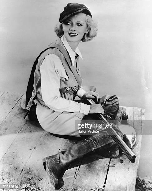 Dressed in a hunting outfit complete with ammunition belt boots and a cap American film actress Bette Davis poses on the edge of a pier with a...