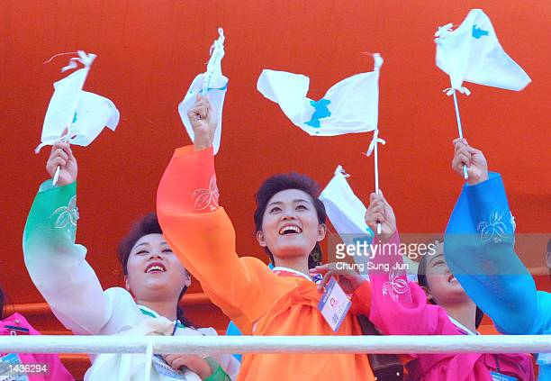Dressed in colorful traditional robes North Korean women wave Unification flags upon their arrival at the Dadaepo port September 28 2002 in Busan...