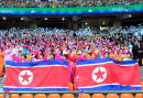 Dressed in colorful traditional robes North Korean women wave North Korea's national flag before the 14th Asian Games opening ceremonies at the main...