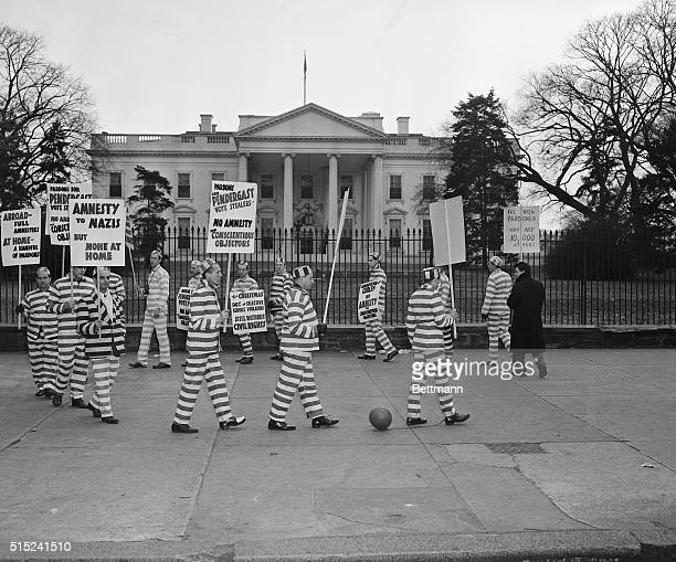 Dressed in prison garb representatives of the Committee for Amnesty based in New York parade in front of the White House carrying posters requesting...