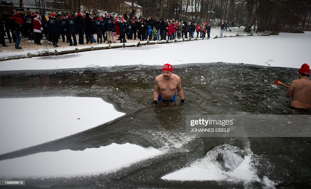 Dressed up winter swimmer prepare a hole in the icy surface of a lake for a traditional ice swimming session on December 23, 2012 in Lanke, some 50 kilometers north of Berlin.