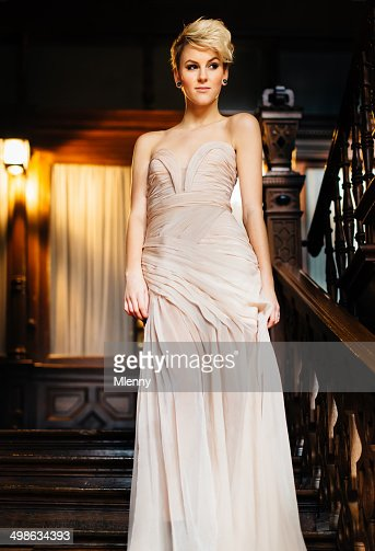 Dressed up woman in evening gown walking stairway to ballroom