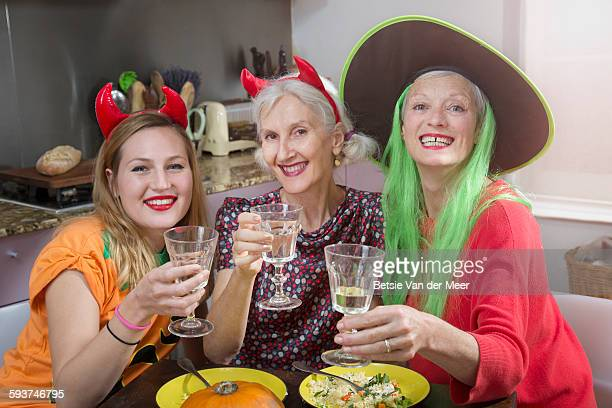 Dressed up women toast at halloween dinner.