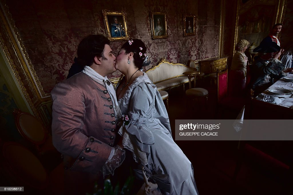 Dressed-up in eighteenth century costumes, a man and woman kiss to celebrate Valentine's Day in one of the rooms of the royal hunting lodge and residence (Palazzina di caccia) built for the Royal House of Savoy in Stupinigi, 10 kms southwest of Turin, northern Italy, on February 14, 2016. / AFP / GIUSEPPE CACACE