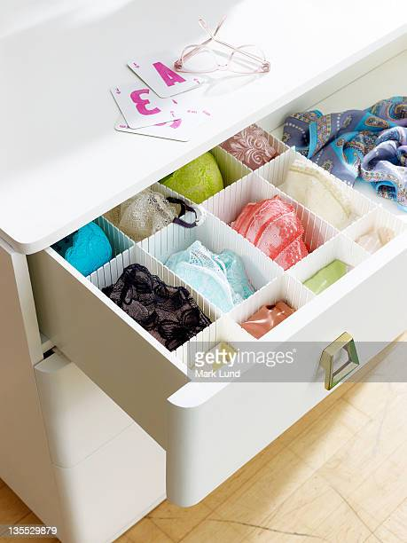 Dresser with underwear, cards and eyeglasses.