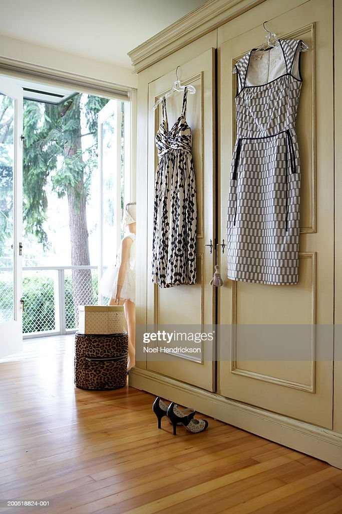 Dresses hanging from closet door : Stock Photo