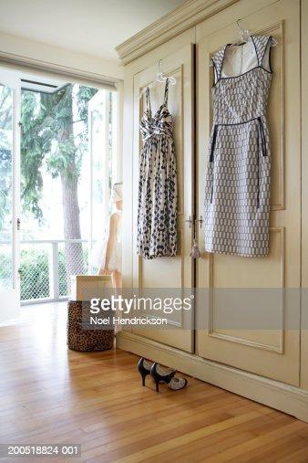 Dresses hanging from closet door : Stock Photo