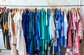 Colorful women's dresses on hangers in a retail shop. Fashion and shopping concept