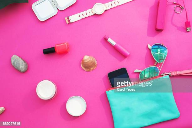 Dressing case with a lot of feminine objects.overhead shot.pink background