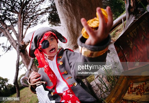 Dressing up Pirate child finding gold coins in treasure chest