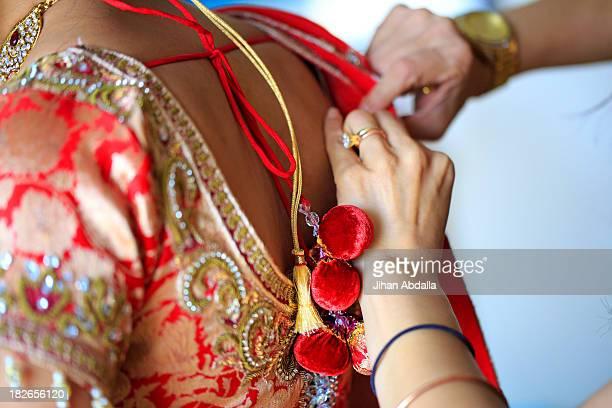 Dressmaker adjusting traditional Indian dress