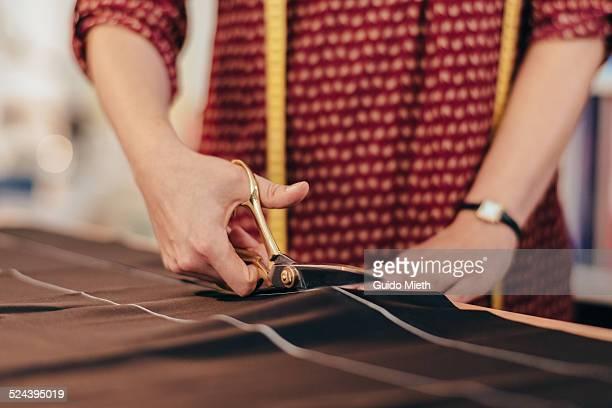 Dressmaker cutting cloth.