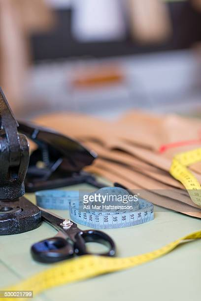 Dressmakers pattern, scissors and tape measure on work table in workshop