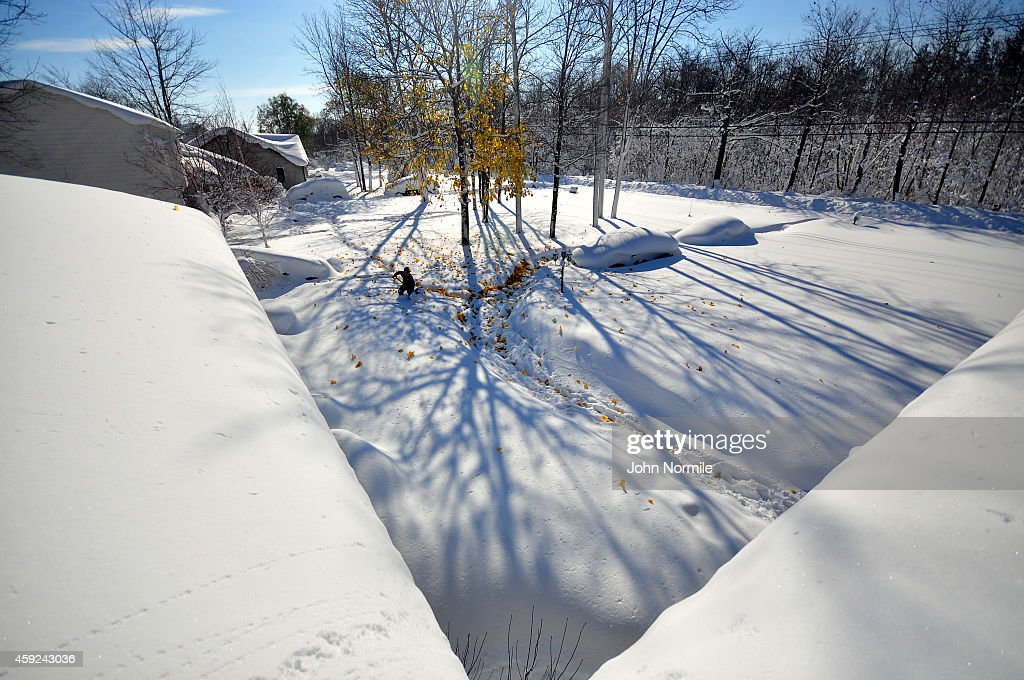 Drew Ahmed makes his way through nearly five feet of snow on November 19 2014 in the Lakeview neighborhood of Buffalo New York The record setting...
