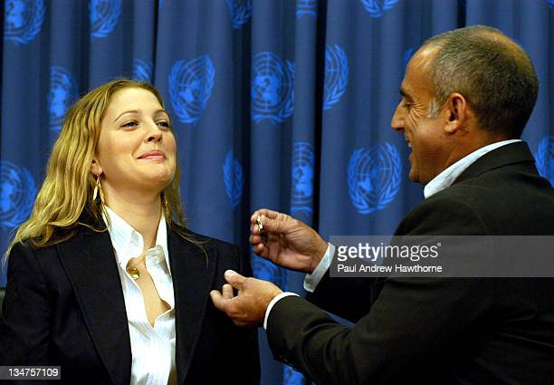 Drew Barrymore has a pin placed on her lapel by Xorin Balbes CoChairman of Artists for the UN as she becomes the first artist to be named 'A Friend...