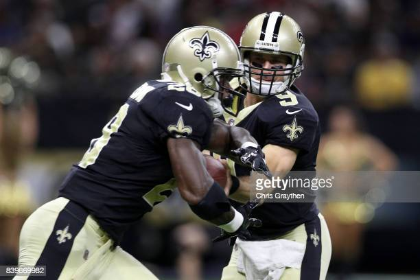 Drew Brees hands the ball to Adrian Peterson of the New Orleans Saints during the game against the Houston Texans at MercedesBenz Superdome on August...