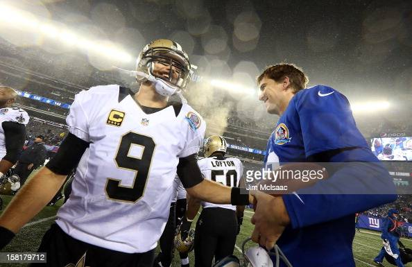 Drew Brees of the New Orleans Saints and Eli Manning of the New York Giants meet after their game at MetLife Stadium on December 9 2012 in East...