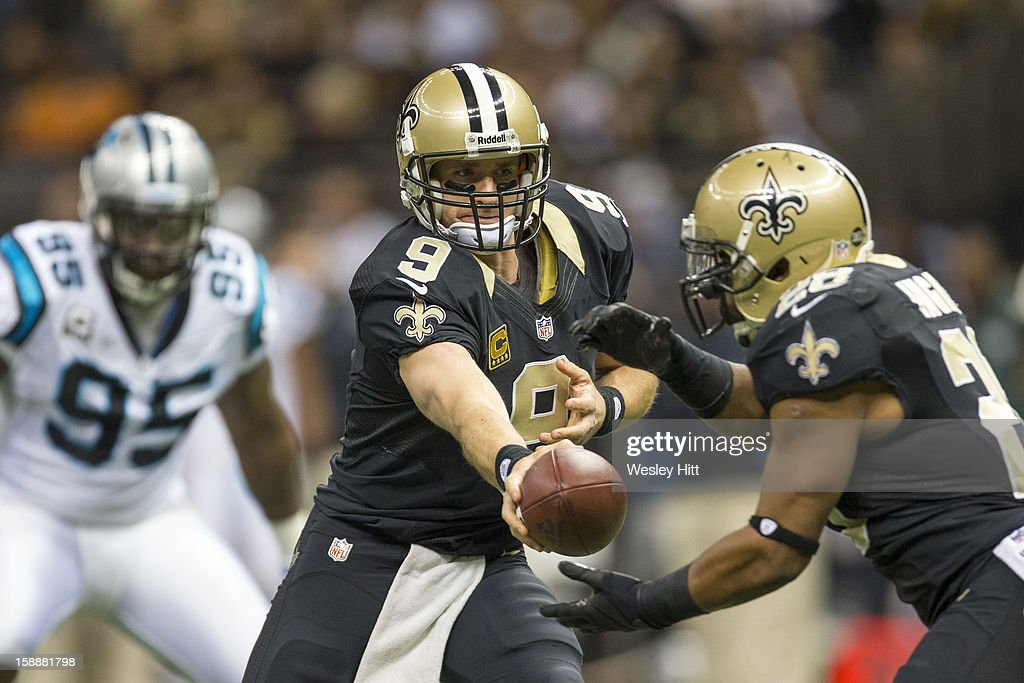 Drew Brees #9 of the New Orleans Saints hands off against the Carolina Panthers at Mercedes-Benz Superdome on December 30, 2012 in New Orleans, Louisiana. The Panthers defeated the Saints 44-38.