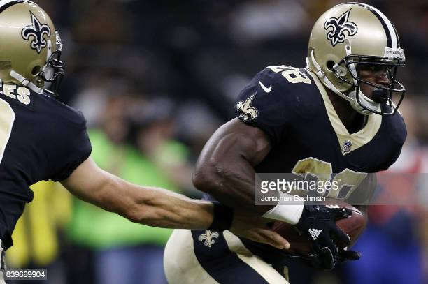 Drew Brees of the New Orleans Saints hands the ball to Adrian Peterson during the first half of a preseason game against the Houston Texans at the...