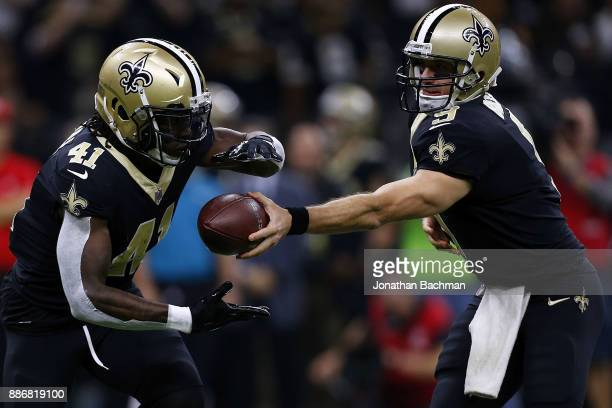 Drew Brees of the New Orleans Saints hands the ball to Alvin Kamara during a game against the Carolina Panthers at the MercedesBenz Superdome on...