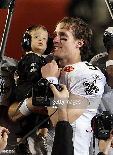 Drew Brees of the New Orleans Saints holds his son Baylen Brees to celebrate after the Saints defeated the Indianapolis Colts during Super Bowl XLIV...