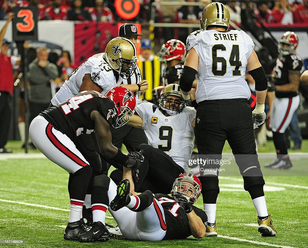 Drew Brees #9 of the New Orleans Saints is helped to his feet after being hit by Kroy Biermann #71 of the Atlanta Falcons at the Georgia Dome on November 29, 2012 in Atlanta, Georgia