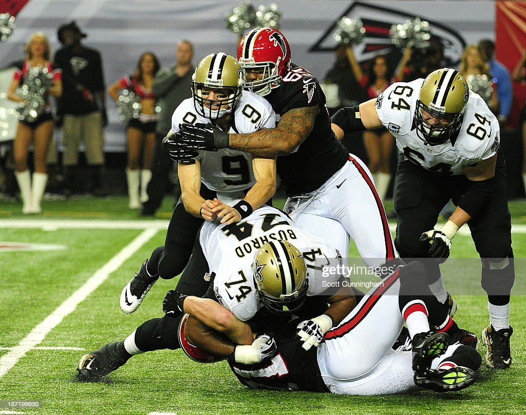 <a gi-track='captionPersonalityLinkClicked' href=/galleries/search?phrase=Drew+Brees&family=editorial&specificpeople=202562 ng-click='$event.stopPropagation()'>Drew Brees</a> #9 of the New Orleans Saints is hit by John Abraham #55 of the Atlanta Falcons at the Georgia Dome on November 29, 2012 in Atlanta, Georgia