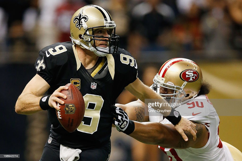 Drew Brees #9 of the New Orleans Saints is pressued by Isaac Sopoaga #90 of the San Francisco 49ers at The Mercedes-Benz Superdome on November 25, 2012 in New Orleans, Louisiana.