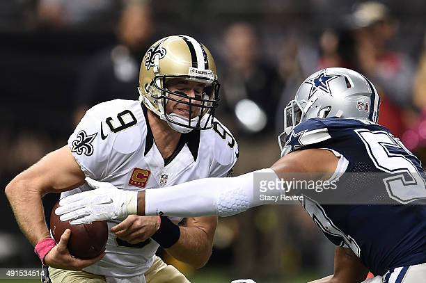 Drew Brees of the New Orleans Saints is pressured by Damien Wilson of the Dallas Cowboys during a game at the MercedesBenz Superdome on October 4...