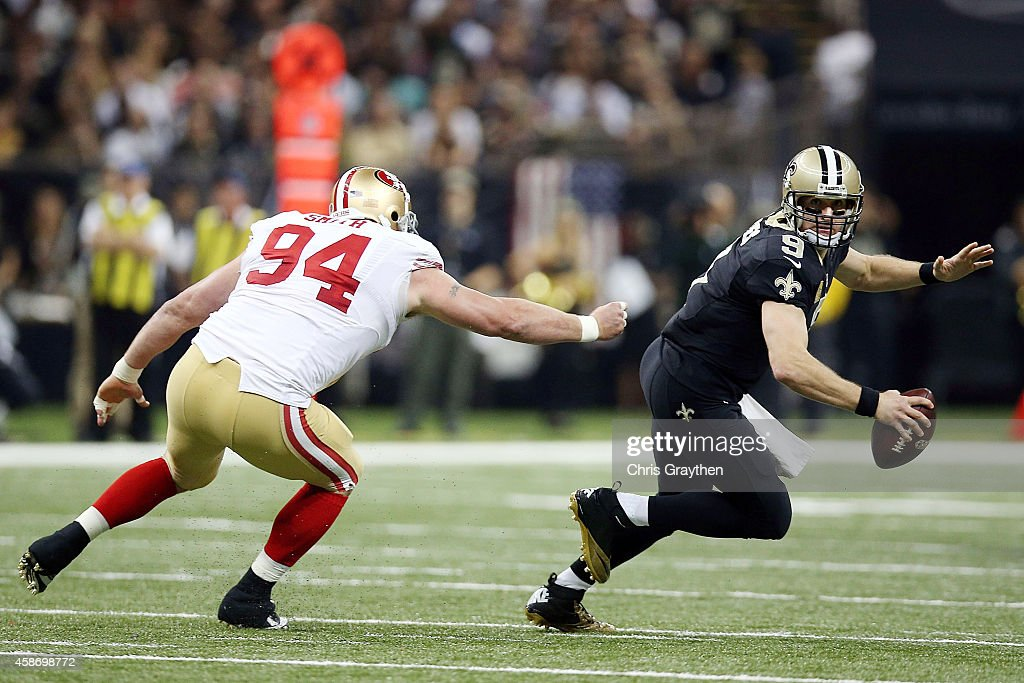 Drew Brees #9 of the New Orleans Saints is pressured by Justin Smith #94 of the San Francisco 49ers during the second quarter of a game at the Mercedes-Benz Superdome on November 9, 2014 in New Orleans, Louisiana.