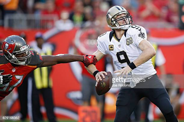 Drew Brees of the New Orleans Saints looks to pass while under pressure from Noah Spence of the Tampa Bay Buccaneers in the first quarter of the game...