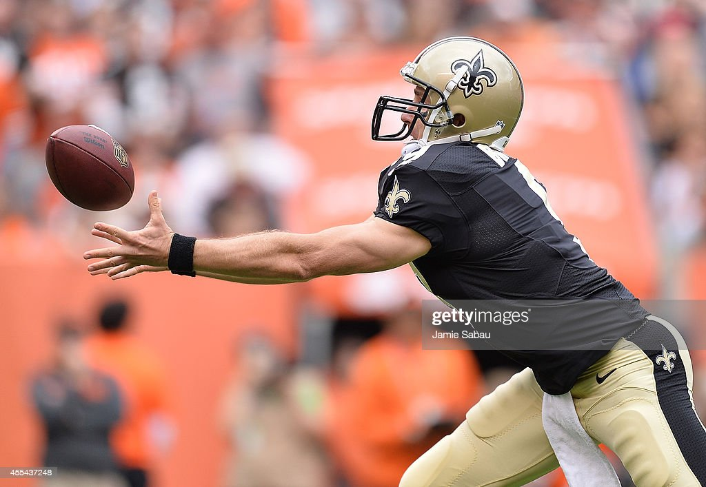 Drew Brees of the New Orleans Saints reaches for the ball after bobbling the snap during the first quarter against the Cleveland Browns at...