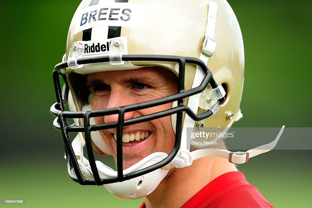 Drew Brees #9 of the New Orleans Saints shares a laugh with teammates following organized team activities, OTA's, at the Saints training facility on May 23, 2013 in Metairie, Louisiana.