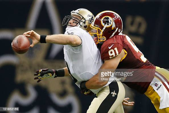 Drew Brees of the New Orleans Saints throws the ball as he is tackled by Ryan Kerrigan of the Washington Redskins during the season opener at...