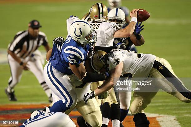 Drew Brees of the New Orleans Saints throws the ball under pressure during Super Bowl XLIV against the Indianapolis Colts at Sun Life Stadium on...