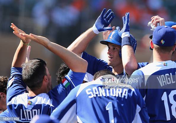 Drew Butera of Italy highfives Alex Liddi after Butera hit a tworun home run against Mexico during the fourth inning of the World Baseball Classic...