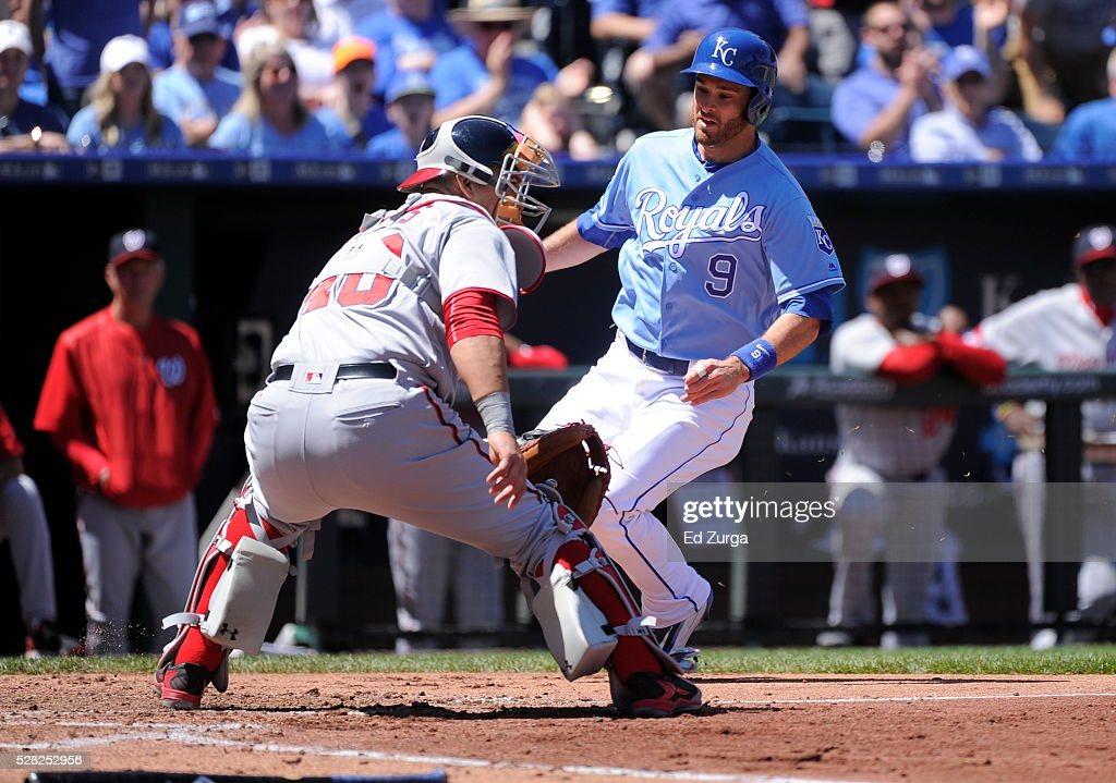 Drew Butera #9 of the Kansas City Royals runs past Wilson Ramos #40 of the Washington Nationals as he scores on a Alcides Escobar single in the second innings at Kauffman Stadium on May 4, 2016 in Kansas City, Missouri.