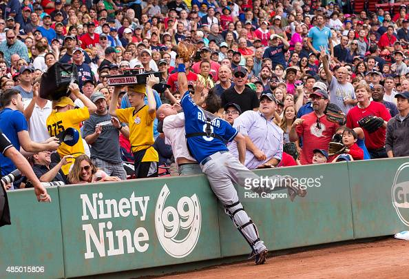 Drew Butera of the Kansas City Royals unsuccessfully leaps into the stands for a foul ball during the first inning against the Boston Red Sox at...