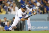 Drew Butera of the Los Angeles Dodgers hits a sacrifice bunt to the pitcher to move Juan Uribe of the Los Angeles Dodgers to second base in the...