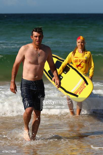 Drew Butera of the Los Angeles Dodgers walks out of the water after swimming with lifesaver Sophie Thomson during a Los Angeles Dodgers players visit...