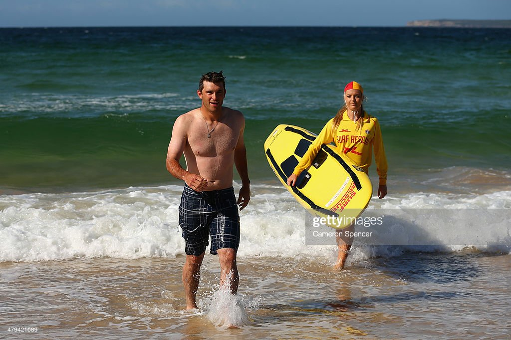 Drew Butera of the Los Angeles Dodgers walks out of the water after swimming with lifesaver Sophie Thomson during a Los Angeles Dodgers players visit at Bondi Beach on March 19, 2014 in Sydney, Australia.