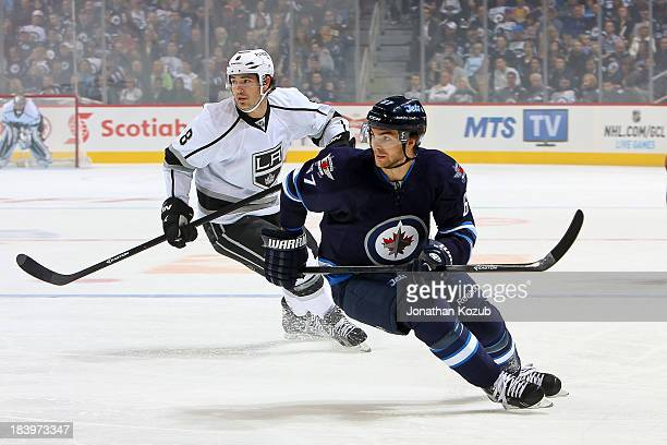 Drew Doughty of the Los Angeles Kings and Michael Frolik of the Winnipeg Jets keep an eye on the play during second period action in the home opener...