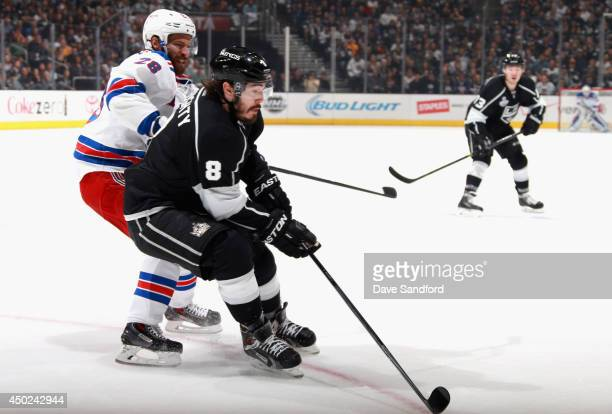 Drew Doughty of the Los Angeles Kings controls the puck away from Dominic Moore of the New York Rangers in the first period of Game Two of the 2014...
