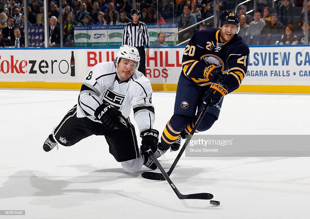 Drew Doughty #8 of the Los Angeles Kings is tripped up as he lunges for the puck against Henrik Tallinder #20 of the Buffalo Sabres at the First Niagara Center on November 12, 2013 in Buffalo, New York. The Sabres defeated the Kings 3-2 in the shootout.