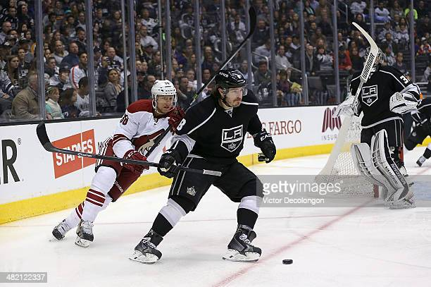 Drew Doughty of the Los Angeles Kings plays the puck away from Rob Klinkhammer of the Phoenix Coyotes in the corner during the first period of their...