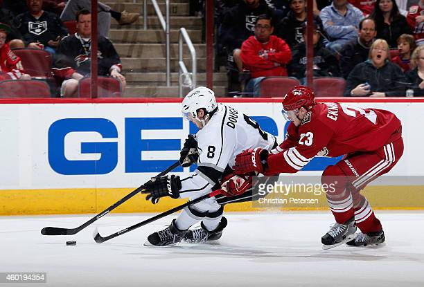 Drew Doughty of the Los Angeles Kings skates with the puck ahead of Oliver EkmanLarsson of the Arizona Coyotes during the NHL game at Gila River...