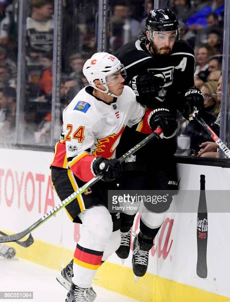 Drew Doughty of the Los Angeles Kings takes a hit from Travis Hamonic of the Calgary Flames during the first period at Staples Center on October 11...