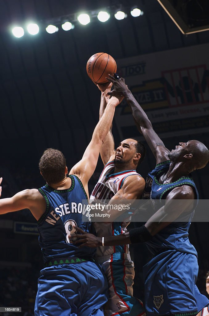 Drew Gooden #0 of the Memphis Grizzlies puts up a shot under pressure by Kevin Garnett #21 and Rasho Nesterovic #8 of the Minnesota Timberwolves during the NBA game at The Pyramid on November 15, 2002 in Memphis, Tennessee. The Timberwolves won 99-95.