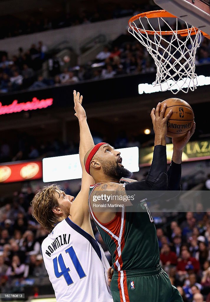 Drew Gooden #0 of the Milwaukee Bucks takes a shot against Dirk Nowitzki #41 of the Dallas Mavericks at American Airlines Center on February 26, 2013 in Dallas, Texas.